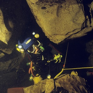 A British cave diver manoeuvres through a sump passage