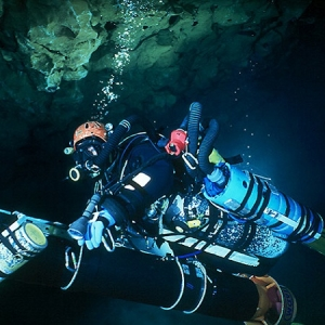 A British cave diver using rebreather and diver propulsion vehicle