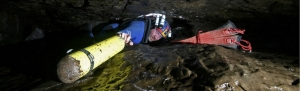 A British cave diver pushes his equipment through a low bedding plane